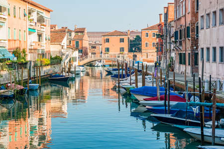Houses and boats along a quiet canal in Giudecca, Venice, Italy.
