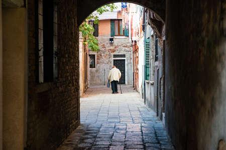 Street life in Venice. Old woman walk in castello district. Standard-Bild