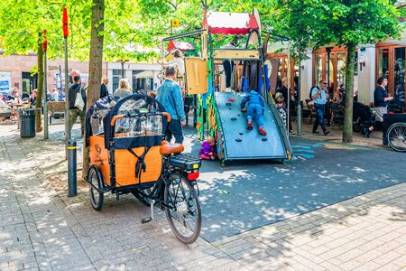 Odense, Denmark - May, 2019: Street life in Odense. People spend time downtown.