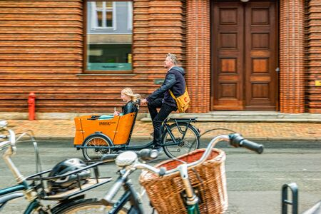 Odense, Denmark - May, 2019: Street life in Odense. Man riding bicycle with trailer for children. Standard-Bild - 136128345
