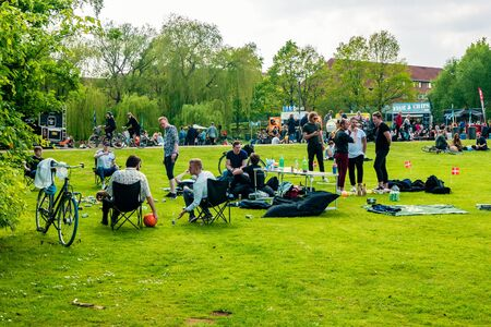 Odense, Denmark - May, 2019: Street life in Odense. People spend time relaxing in the park.