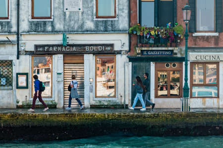 Venice, Italy - October, 2019: Street life in Venice. People walk along the facade of building next to the waterfront of the lagoon on Giudecca island.