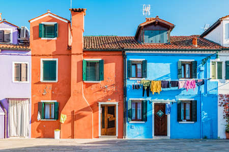 Venice, Italy - October, 2019: Typical colorful house of Burano Island with hanging laundry at its facade