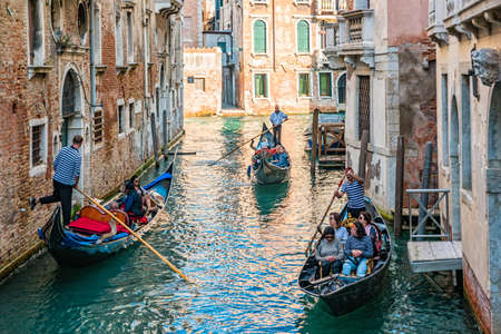 Venice, Italy - October, 2019: Gondolier on a gondola on canal street in Venice, Italy. Editorial