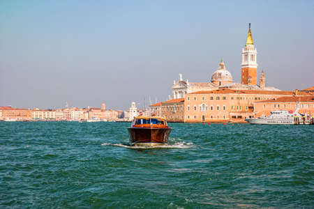 Venice, Italy - October, 2019: Water taxi sails venetian lagoon in Italy. Editorial