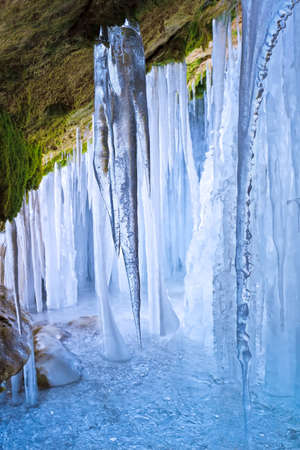 frost covered: Inside a cascade of ice with icicles and moss on the rocks Stock Photo
