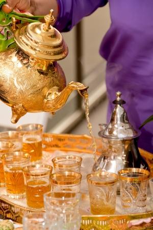 marocchini: Vassoio con tazze di t� ornato, teiera d'oro in una casa da t� in Marocco Archivio Fotografico