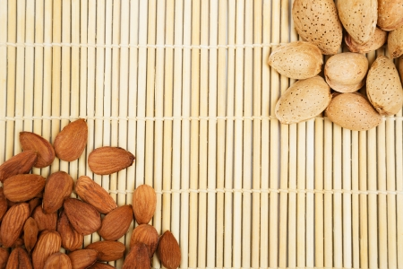 Almonds in a background tablecloth, snacks of nuts in shell and seeds Stock Photo