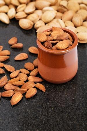 Almendras en un recipiente, snacks de nueces, almendras con c�scara Foto de archivo