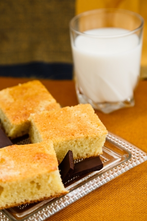 Portions of homemade cake with chocolate and glass of milk for breakfast or snack