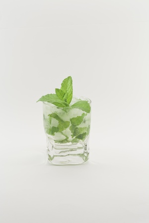 Glass of cocktail made with white rum, lime juice, mint, sugar, ice, soda and a few drops of angostura on white background photo