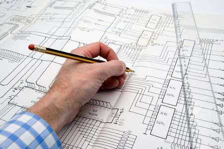 debugging: Engineer working on a project with pencil and ruler