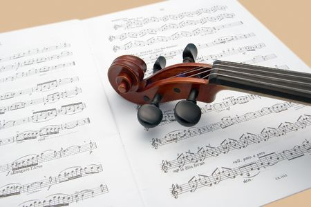 rehearse: Violin neck resting on music scores