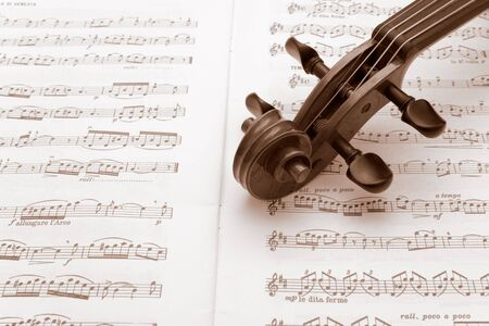 rehearse: Vintage violin neck resting on a sheet music Stock Photo