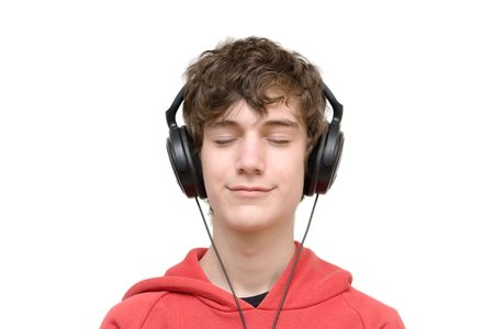 Teenager listening music with headphones isolated on pure white photo