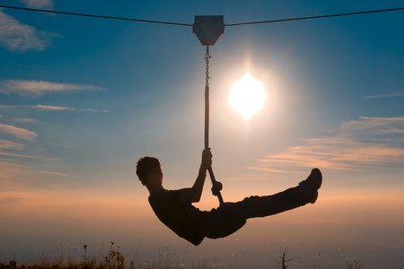 traverse: silhouette of a boy playing with a tyrolean traverse Stock Photo