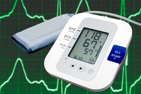 Digital blood pressure monitor with cardiogram in the background photo