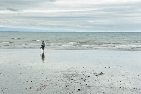 Woman at Criccieth beach in Wales, UK photo