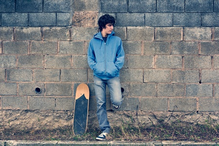 skateboarding: Young handsome boy in urban background Stock Photo