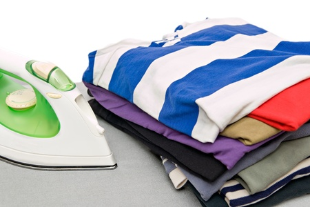 Stack of colorful clothes and electric iron  photo