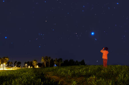 Kid looking at the stars with binoculars photo
