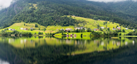 fiord: Small village reflection on the banks of a fiord in Norway Stock Photo