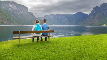 hardanger: Mother and son sitting on a bench  looking at the fjord in Ulvik,  Norway