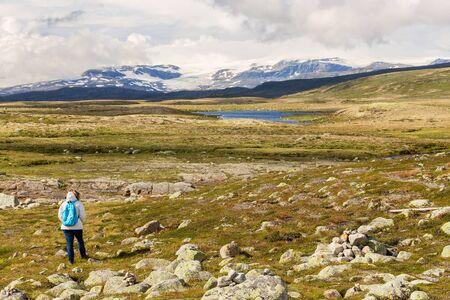 hardanger: Woman looking at the Hardangervidda National Park landscape Stock Photo