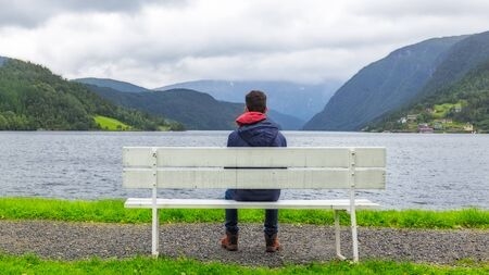 hardanger: Boy sitting on a bench  looking at the fjord in Ulvik,  Norway Stock Photo