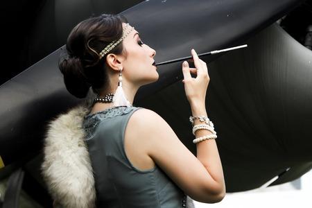 militaire sexy: Retro portrait d'une femme avec embout buccal et de la fourrure et hélice d'avion à l'arrière-plan Banque d'images