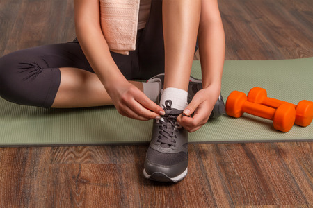 fit girl: Beautiful athletic girl tying shoelaces, sitting on a mat. close-up