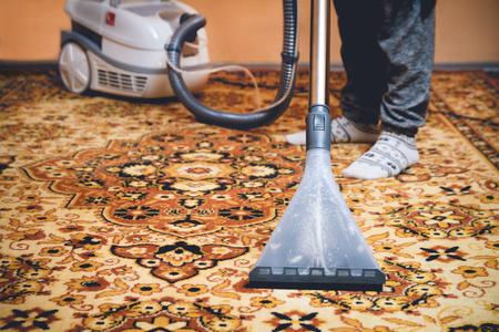 Kobieta czyszczenia perski dywan przez przemycie odkurzacz