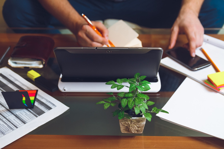 telework: A man sitting at a desk, writing a pencil in a notebook . Telework concept