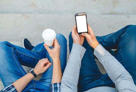hombres jovenes: Dos hombres jóvenes con el teléfono en la mano sentado en los escalones. vista superior Foto de archivo