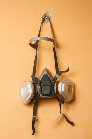respirator: Respirator mask on the wall. Copy space Stock Photo