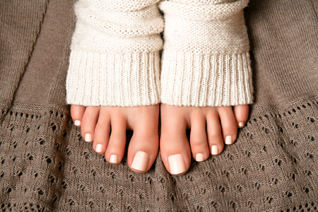 girl socks: Beautiful beige pedicure. Feet in soft knitted socks on a brown plaid lace