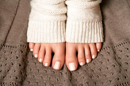 beautiful feet: Beautiful beige pedicure. Feet in soft knitted socks on a brown plaid lace