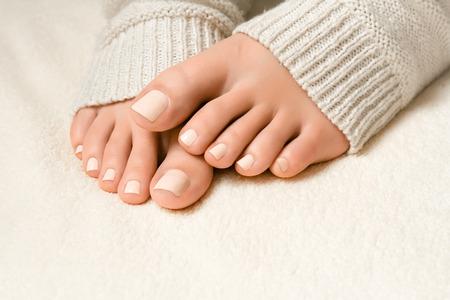 Mooie witte pedicure. Voeten in zachte gebreide sokken op de plaid