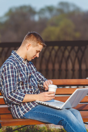 distant work: Young male businessman with the notebook. The concept of remote working outdoors