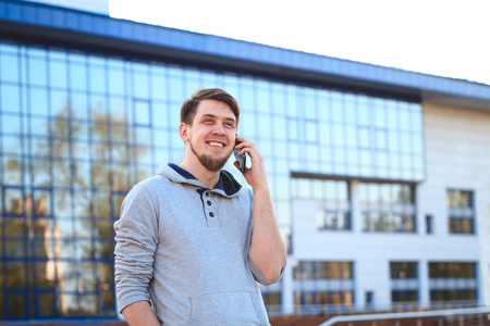 informal clothes: Portrait of a young man in casual clothes with a phone on the background of the business center. The informal business, free business concept