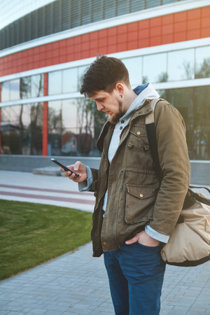 emerged: Portrait of a young man emerged from the airport with a phone in his hand and a bag. Stock Photo