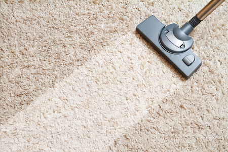mite: include the long beige carpet cleaning with a vacuum cleaner Stock Photo
