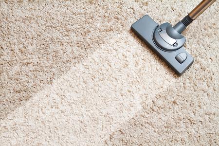 mujer limpiando: incluir el tiempo de limpieza de alfombras de color beige con una aspiradora Foto de archivo