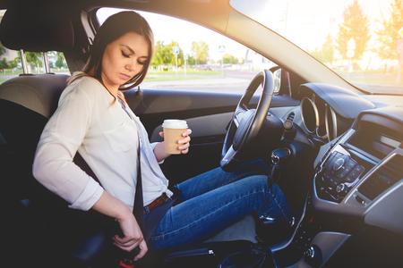 Jonge mooie vrouw besturen van een auto veiligheidsgordel met een kopje koffie in de hand Stockfoto