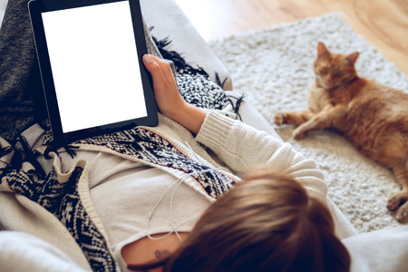 sprawled: Woman in home cozy clothes lying on a sofa using tablet with headphones, looking at a lazy red cat sprawled on the carpet beside. Online education concept. e-learning. back view. Pet shop concept