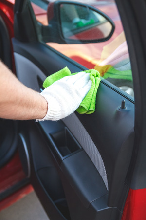 rag wheel: Man wearing gloves to clean the dashboard of the car. Auto Service