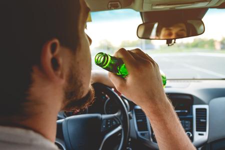 Dronken jonge man het besturen van een auto met een flesje bier. Niet drinken en rijden concept. Rijden onder invloed. DUI, rijden onder invloed. DWI