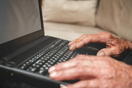 progressive: Senior sitting on the couch with a laptop in hand. mock up. Progressive elderly man Stock Photo