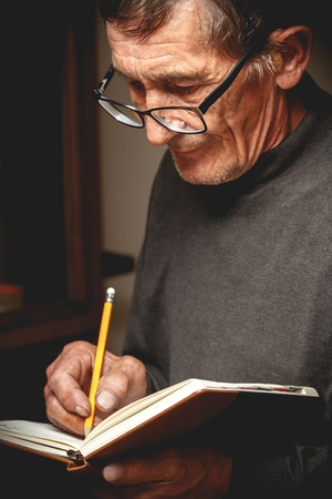 wrote: An elderly man wrote in pencil in a notebook. Photo in low key Stock Photo