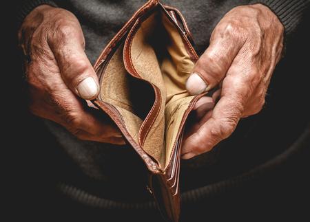 Empty wallet in the hands of an elderly man. Poverty in retirement concept Foto de archivo